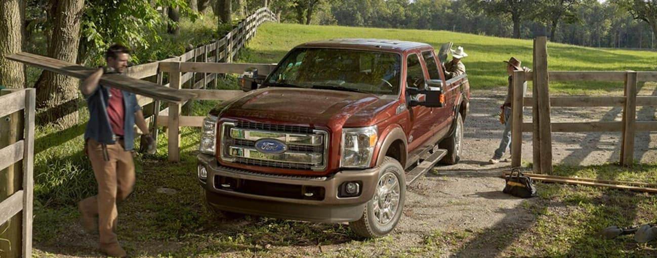 A red 2015 Ford F-250 is parked on a farm while a man is working around it.