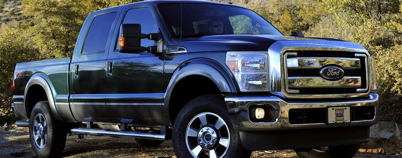 A green 2011 Ford F-250 is parked in the shade next to trees.