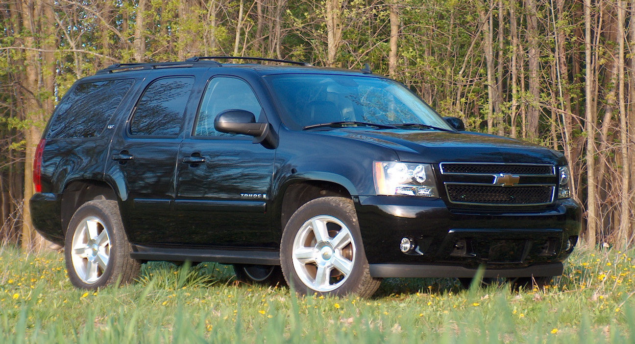 A Black 2007 Used Chevy Tahoe is parked in front of trees near Cincinnati, OH.
