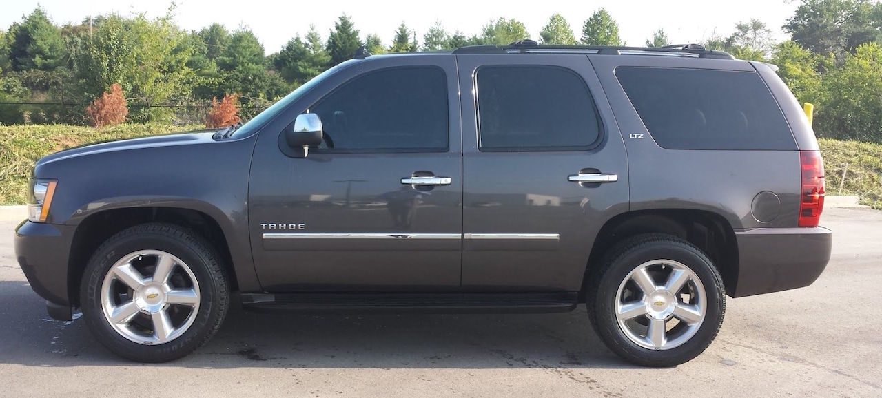 Profile of a Gray 2008 chevy Tahoe ltz 4x4 for sale in front of trees.