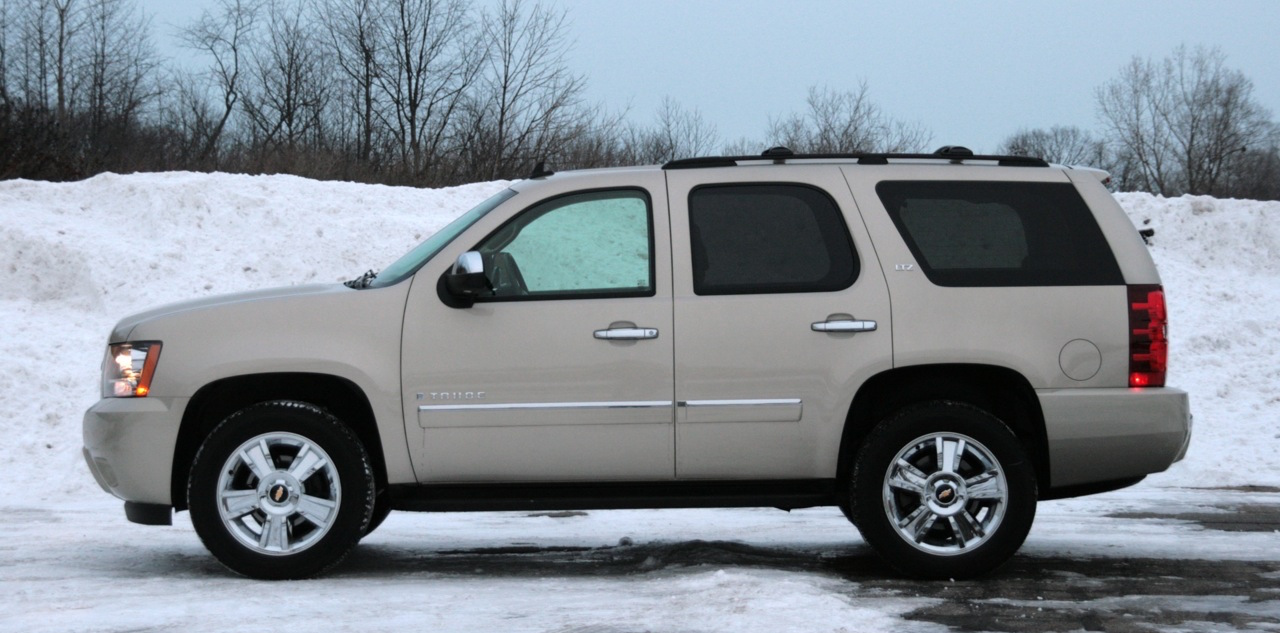 Profile of a White 2009 Used Chevy Tahoe in the snow.