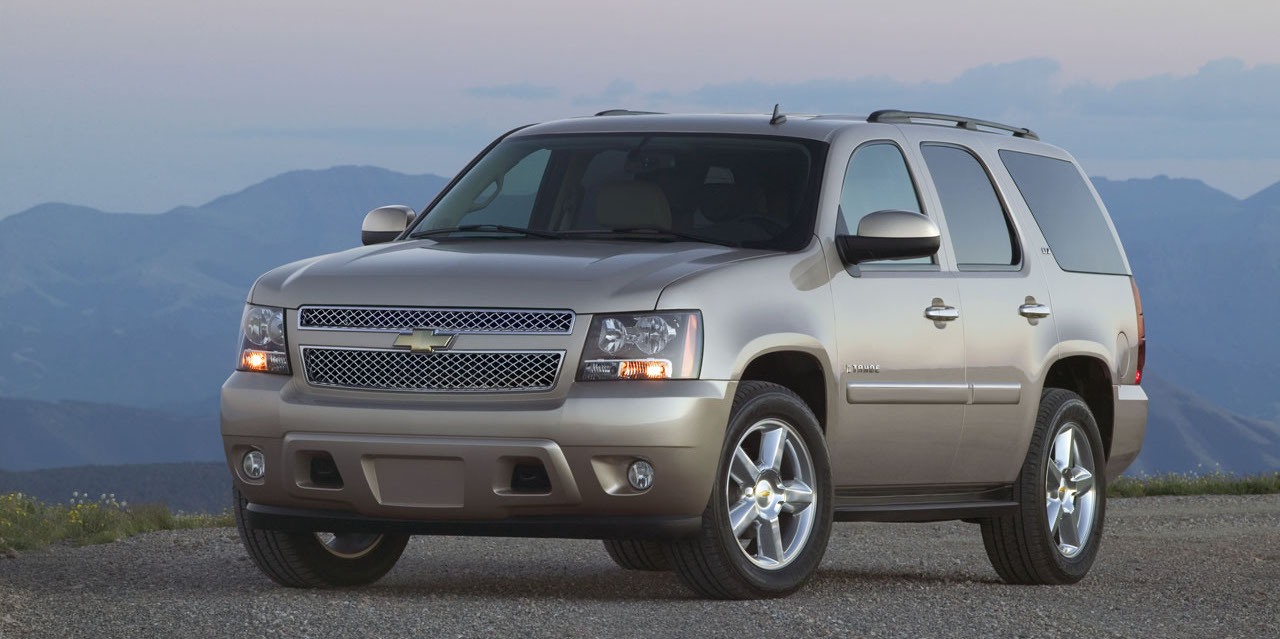 Gold 2010 Chevrolet Tahoe LTZ with mountains in the distance.