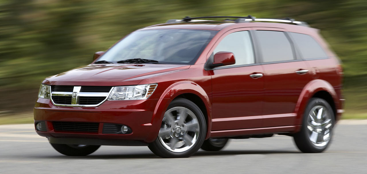 Red 2010 Dodge Journey driving on a tree-lined road