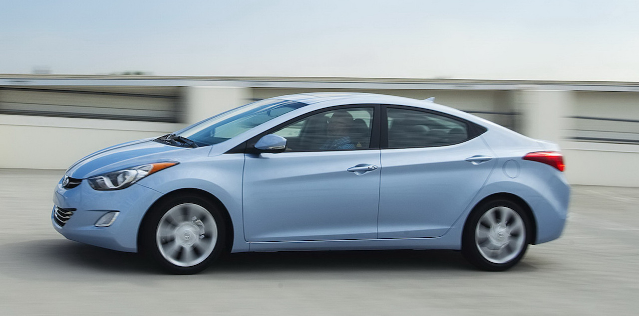 Light blue 2011 Used Hyundai Elantra driving up a parking garage
