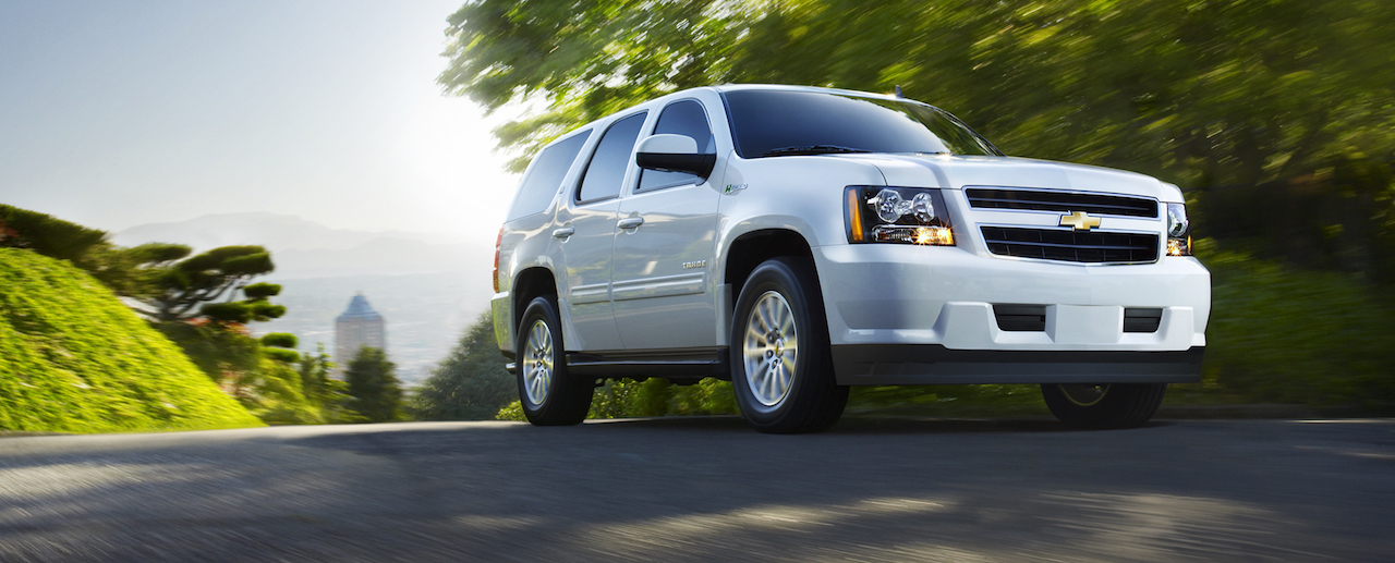 White 2011 Chevy Tahoe driving on a sunny tree-lined road.