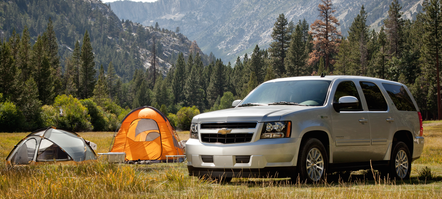 Silver 2012 Chevy Tahoe Hybrid next to tents in the mountain wilderness.