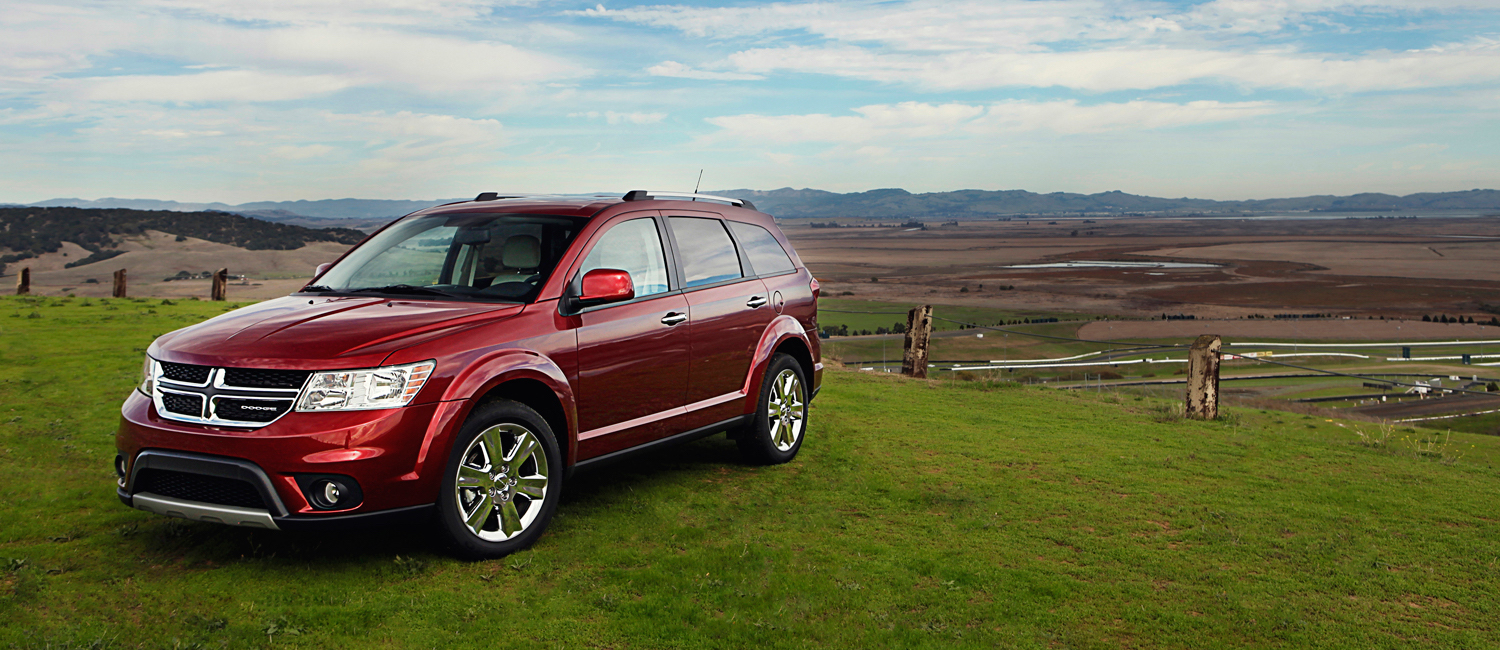 Red 2012 Used Dodge Journey on a hill overlooking fields