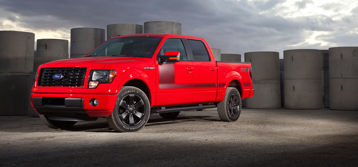 Red 2012 Used Ford F-150 with black stripes on side parked in industrial park with gray cloudy sky