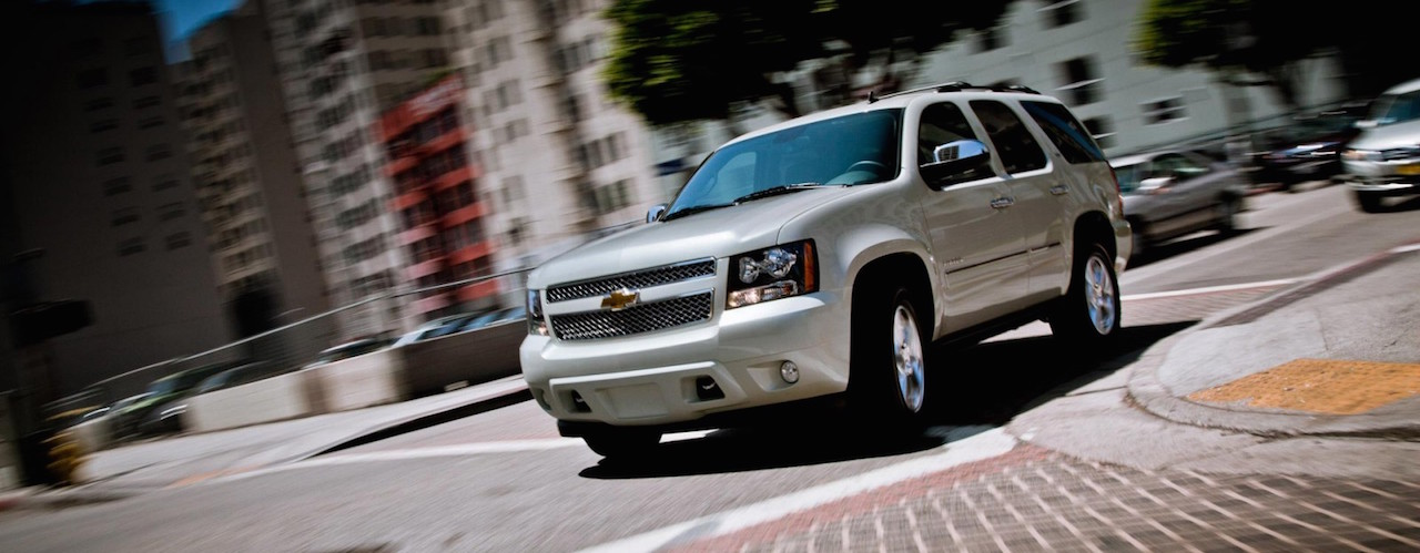 White 2014 Used Chevy Tahoe rounding a city corner.