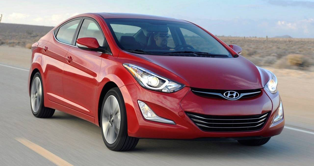 Red 2014 Used Hyundai Elantra driving in a desert