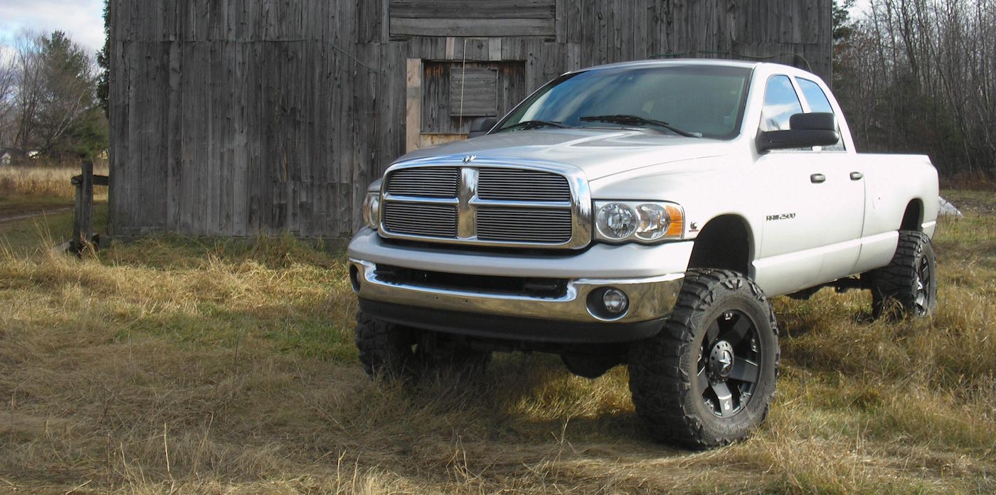 Lifted White 2003 Dodge RAM 2500 in front of barn