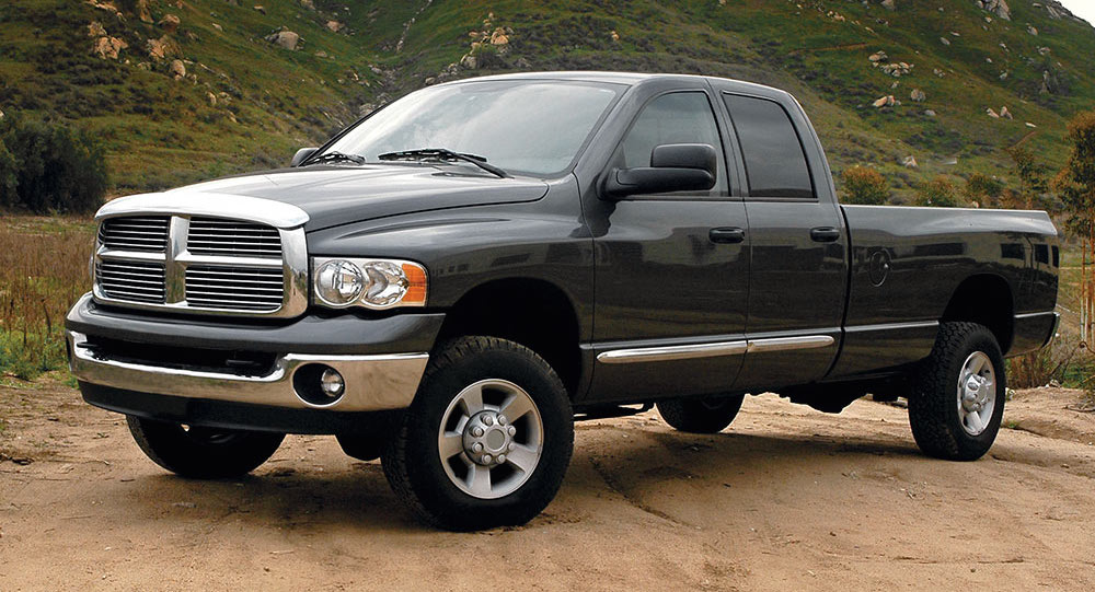 Black 2004 Used Dodge RAM 2500 in front of a grassy mountain