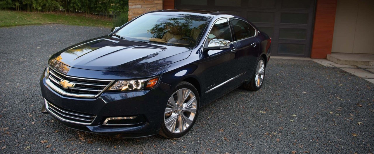 Dark blue Used 2015 Chevy Impala in front of a modern garage