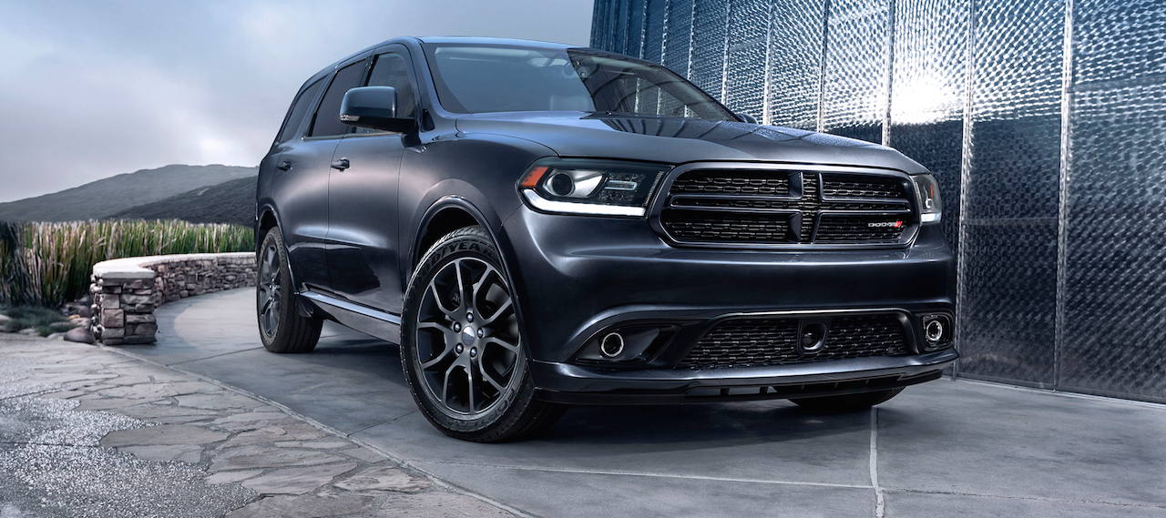 Black 2016 Used Dodge Durango outside modern home with mountains in distance