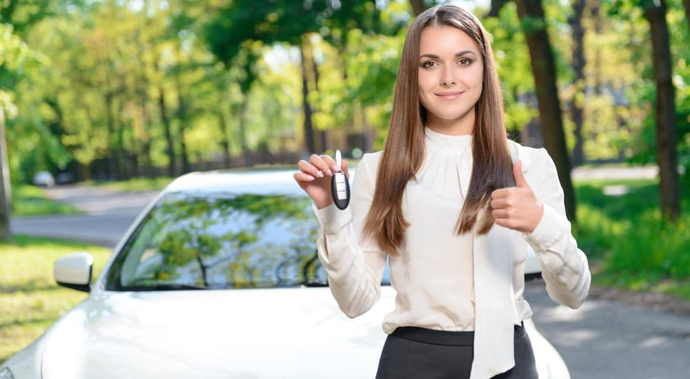 Woman in a white blouse and black skirt giving a thumbs up and holding up a car key in front of a silver sedan
