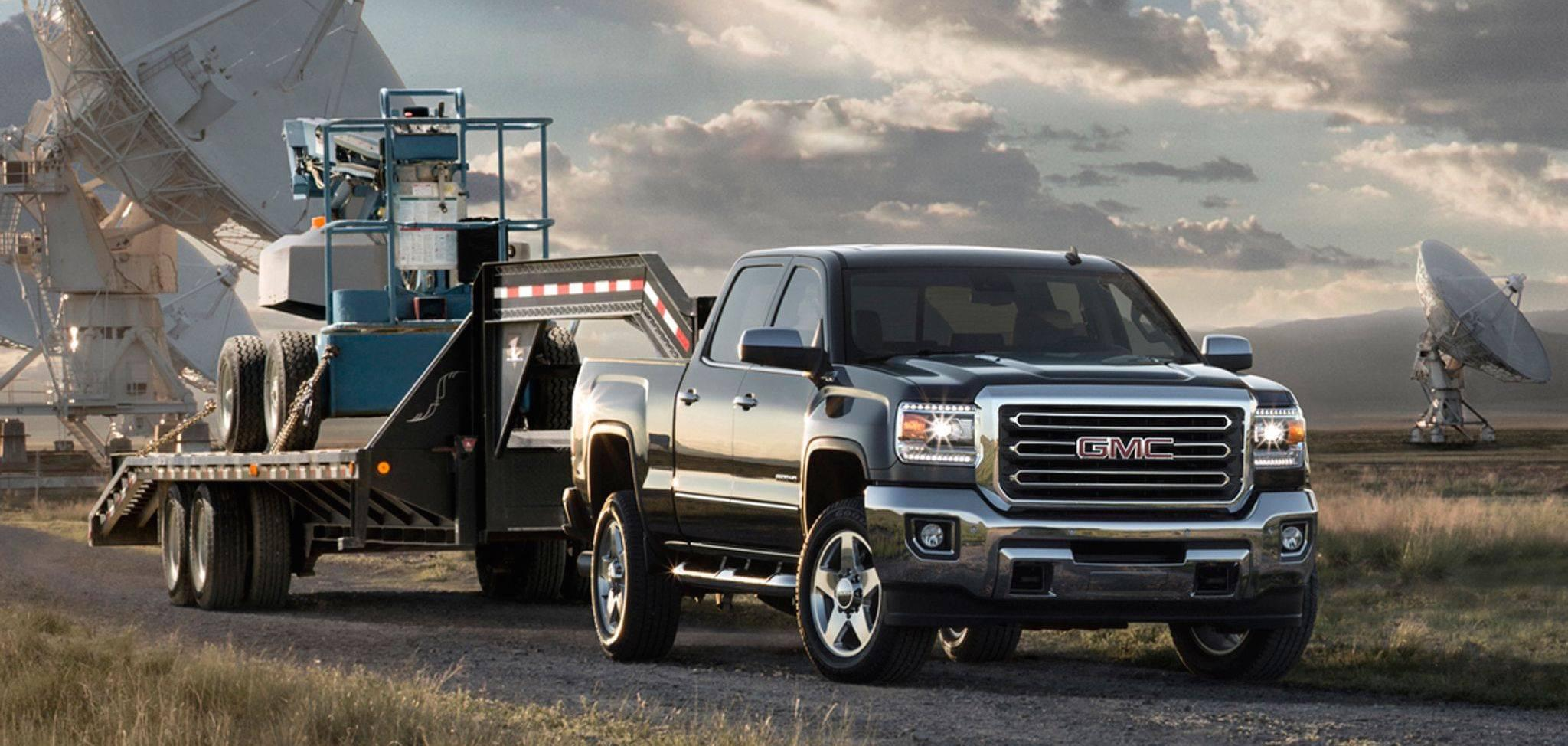 Black 2015 Used GMC Sierra 2500HD towing machinery in front of large satellites