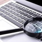 Black magnifying glass laying on the keyboard of a silver laptop