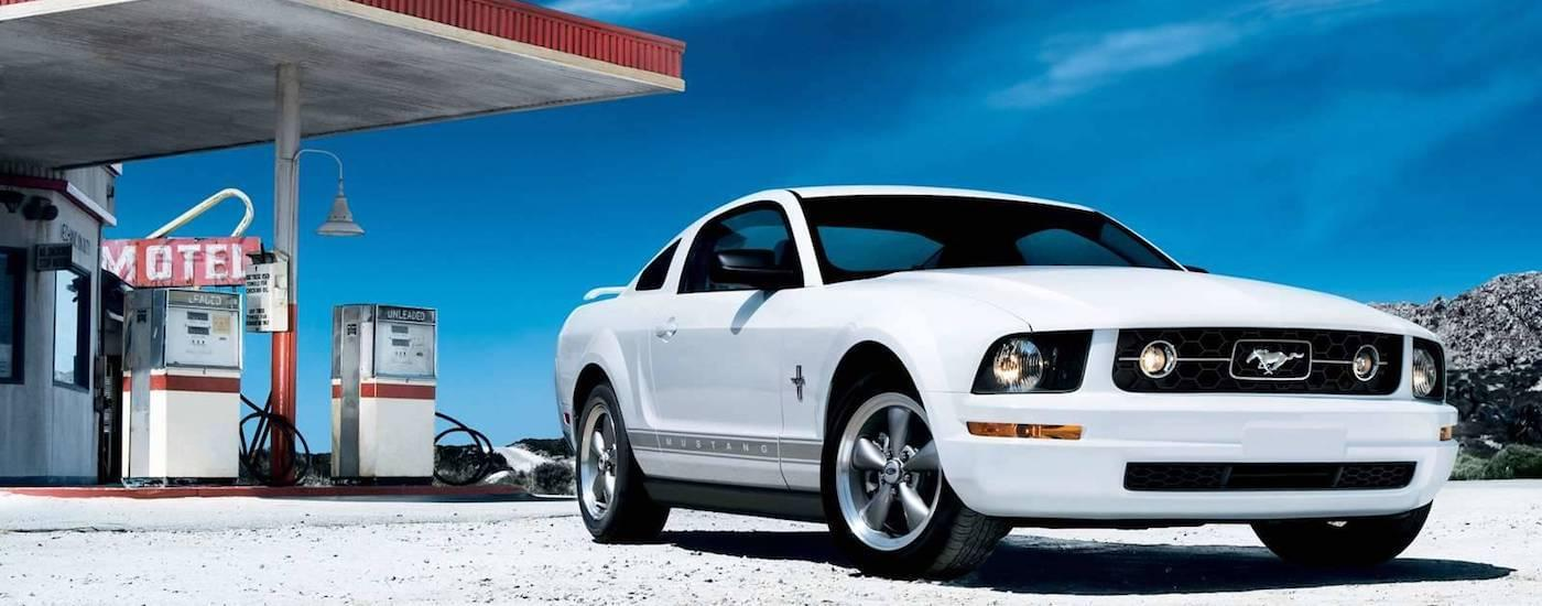 White 2006 Used Ford Mustang parked in front of a desert gas station and motel sign
