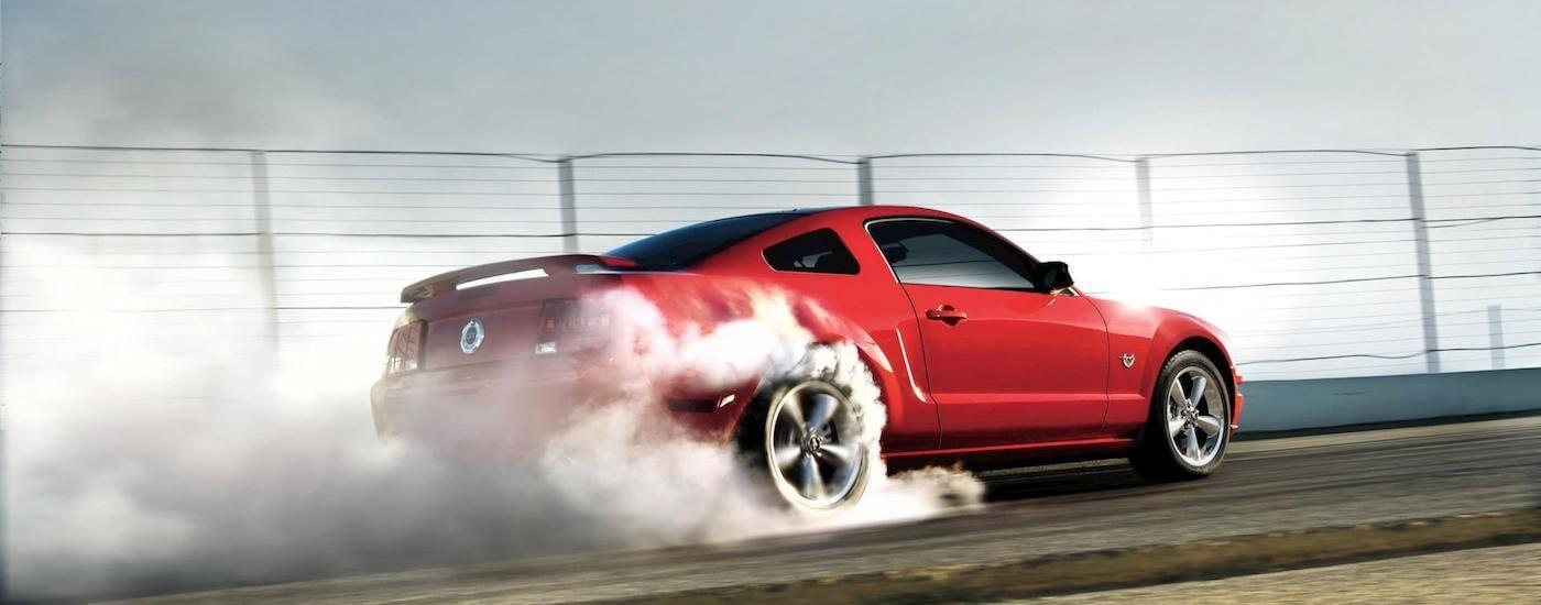 Red 2009 Used Ford Mustang doing a burnout on a track