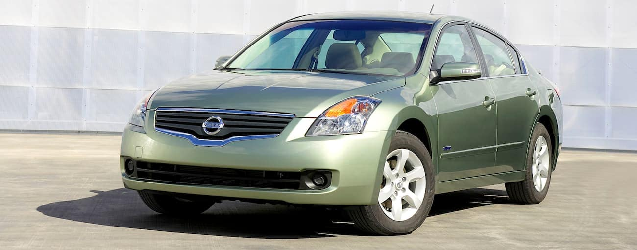 A green 2007 used Nissan Altima in front of a shipping container