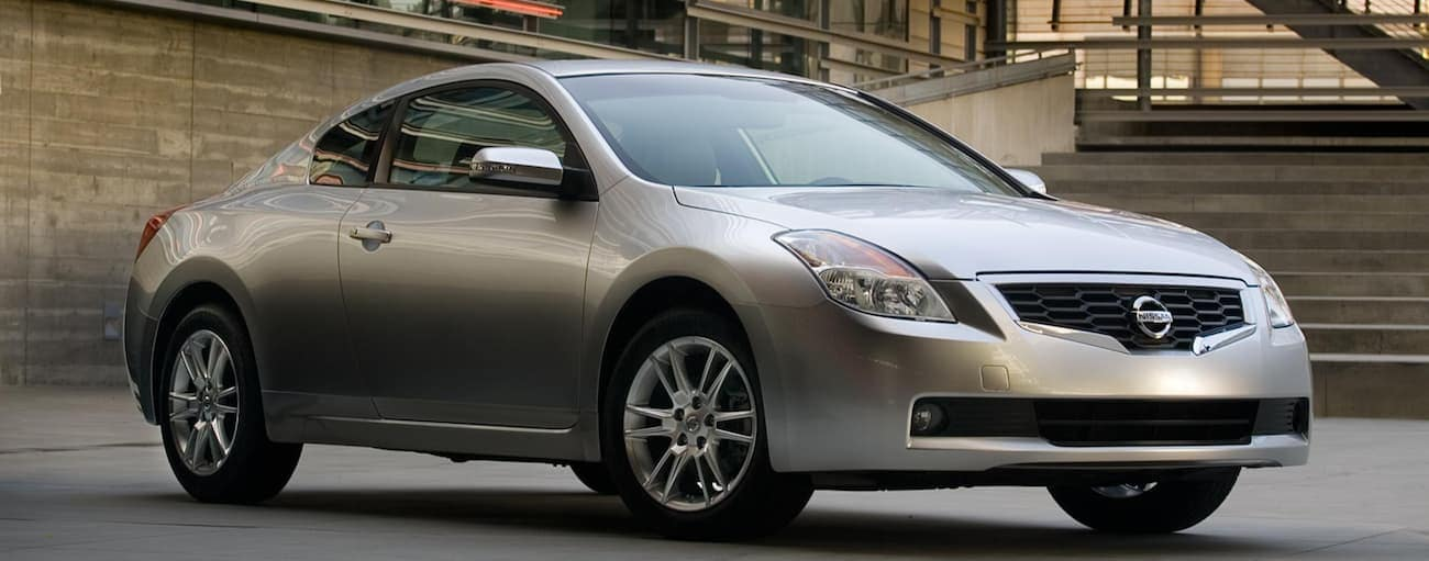 A silver 2008 used Nissan Altima coupe in front of concrete stairs