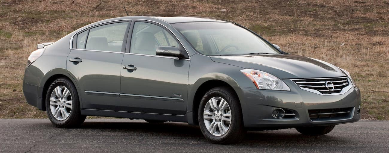 A gray 2011 used Nissan Altima in front of a grassy hill