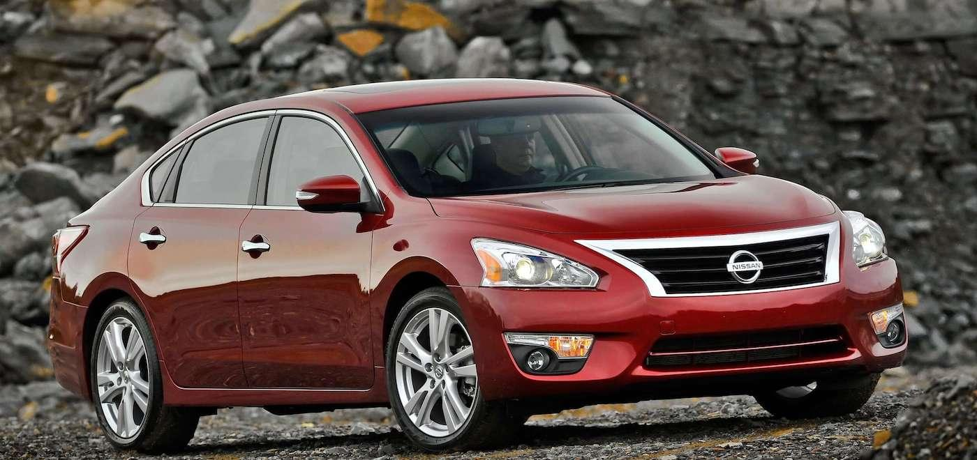 A red 2013 Used Nissan Altima in a gravel pit