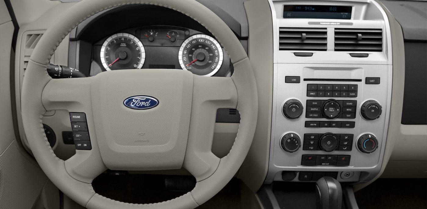 Closeup of steering wheel and light gray interior of a 2011 Used Ford Escape