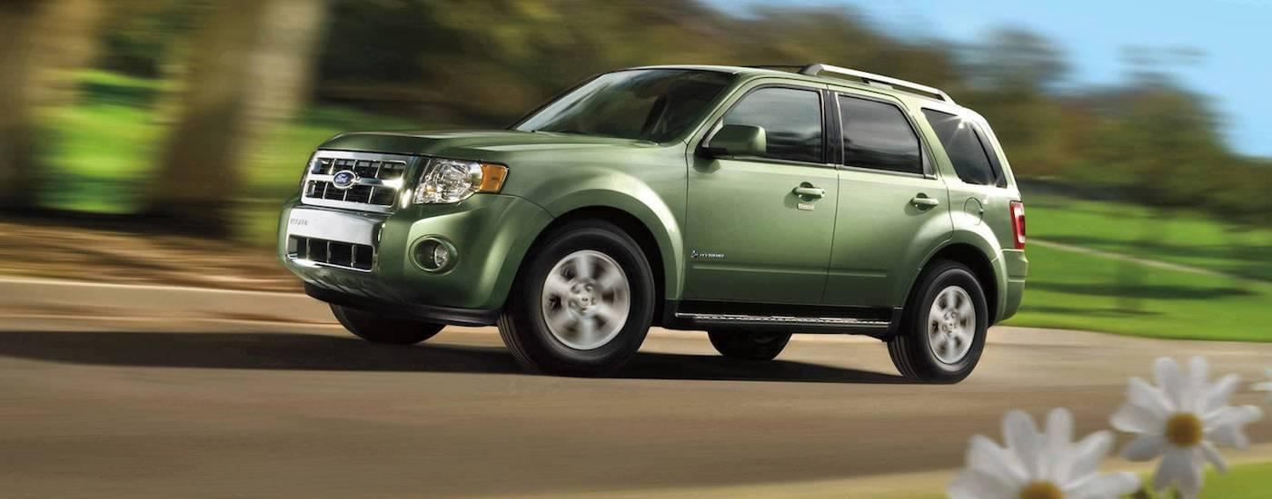 Green 2010 Used Ford Escape driving by park in spring