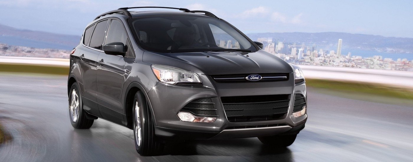 Gray 2015 Used Ford Escape driving away from a city