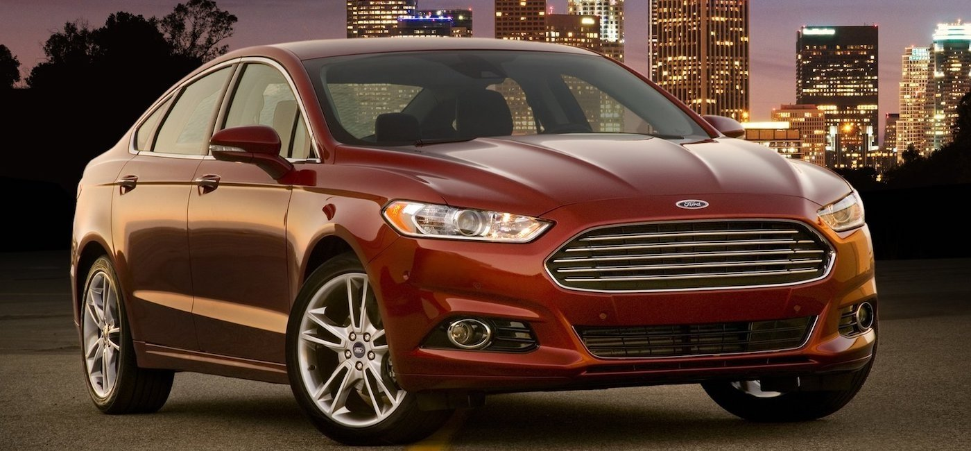 Red 2013 Used Ford Fusion in a city street at night