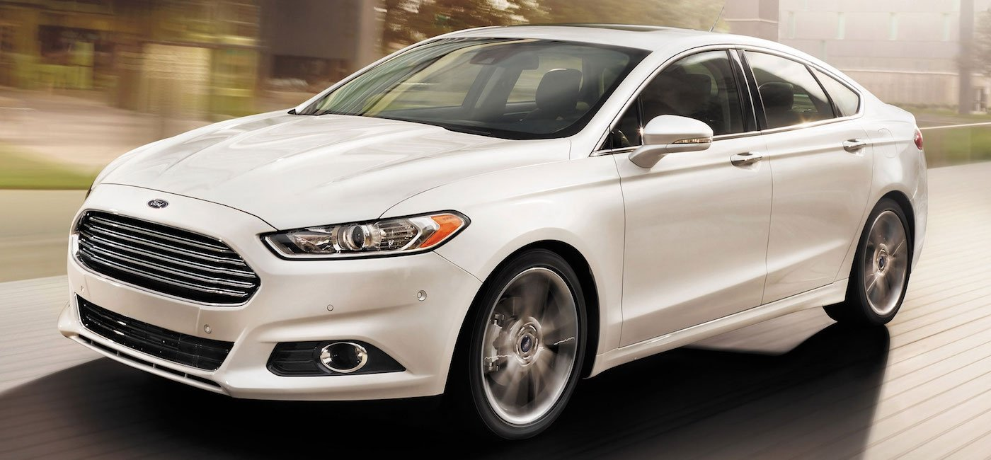 White 2015 Used Ford Fusion driving on city street