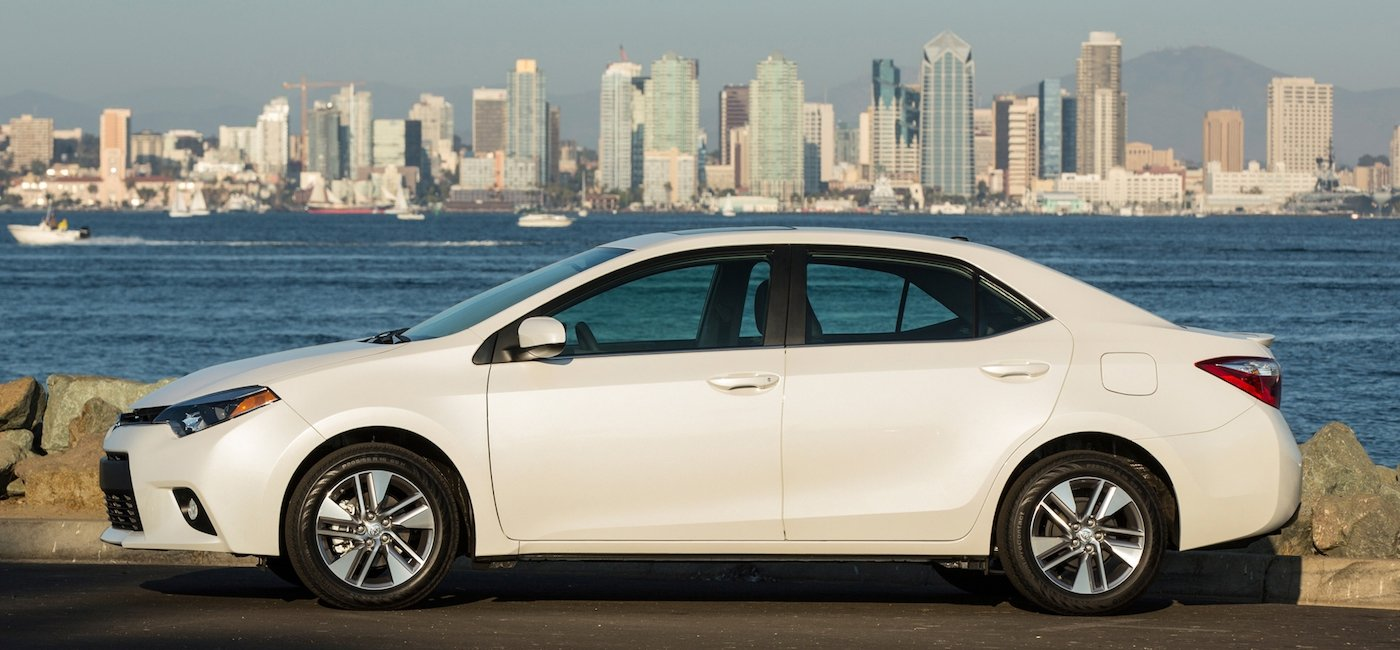 White 2015 Used Toyota Corolla in front of water and city skyline