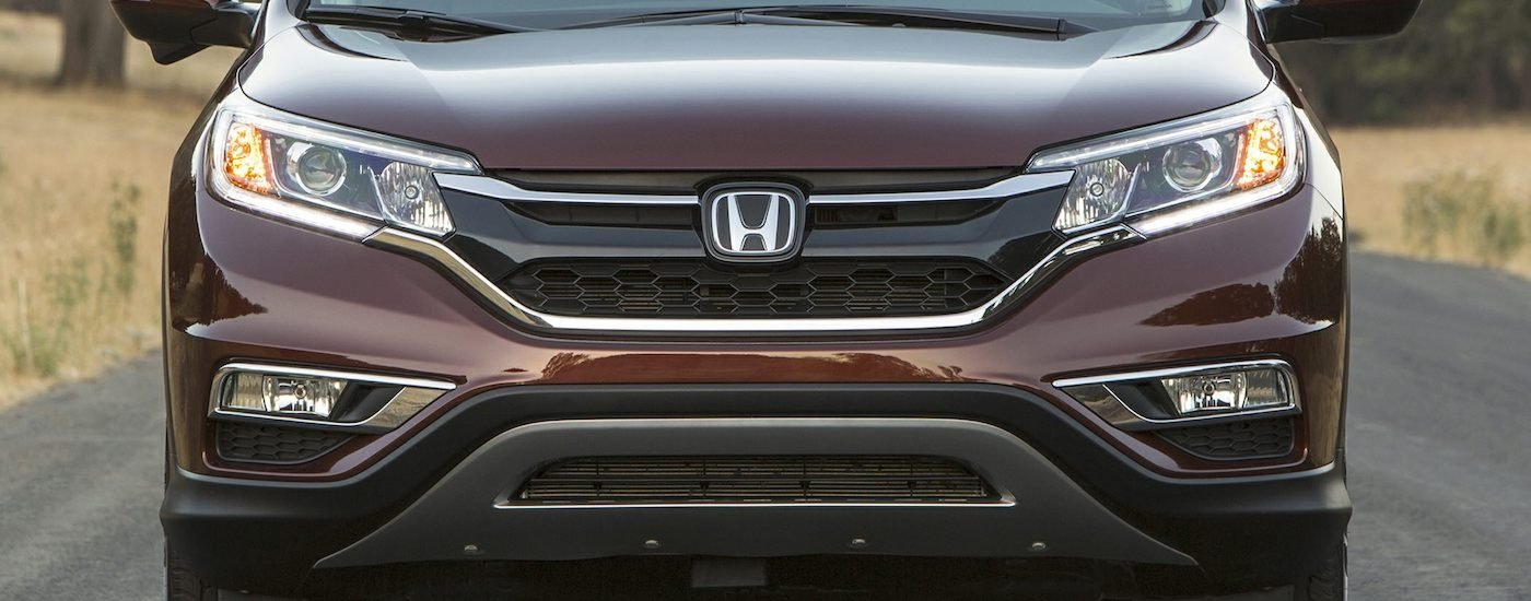 Closeup of Brown 2016 Used Honda CR-V from the front driving on country road