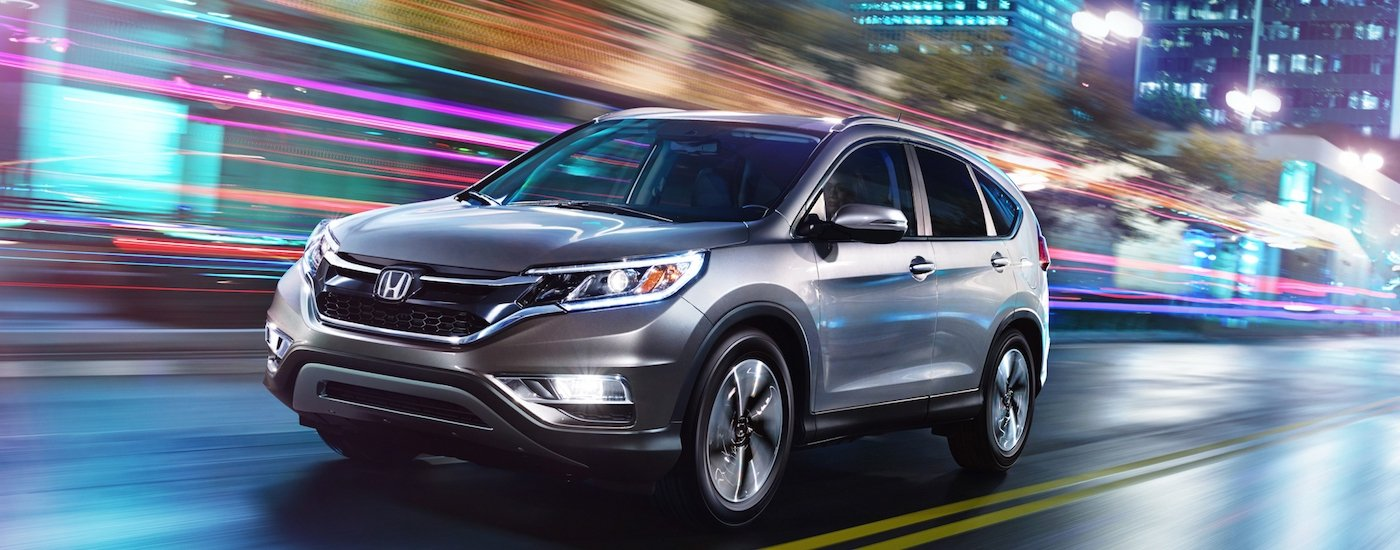 Surreal Image of silver 2016 Used Honda CR-V driving in a city street