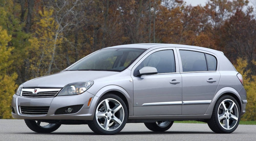 A silver 2008 Saturn Astra is parked in front of fall trees.