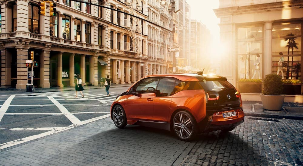 An orange 2014 BMW i3 is driving on a city street at sunset.