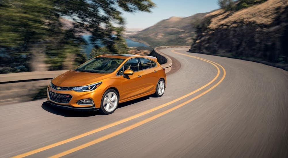 An orange 2018 Chevy Cruze Hatchback is driving on a winding road, find one at you local used car dealer.