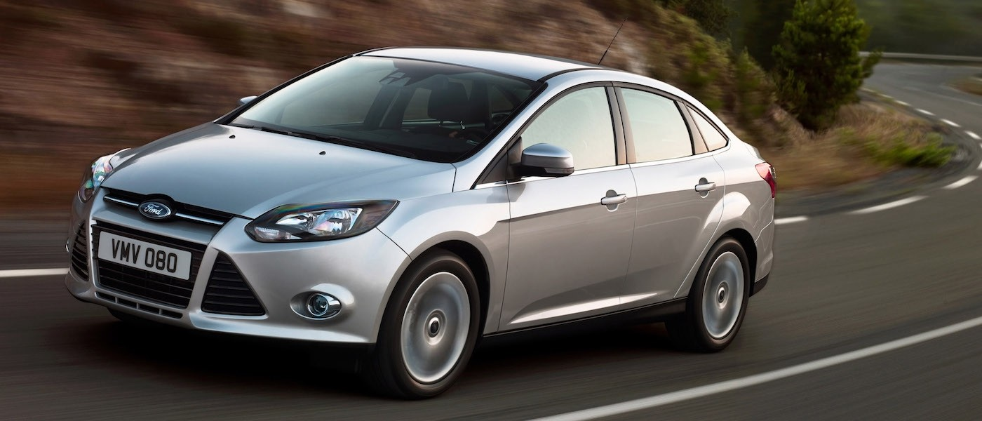 Silver 2012 Used Ford Focus Sedan driving on a winding road