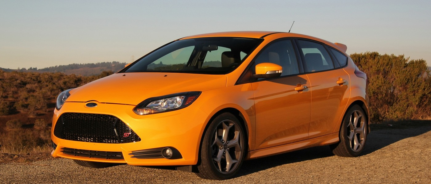 Orange 2014 Used Ford Focus parked at sunset in a field