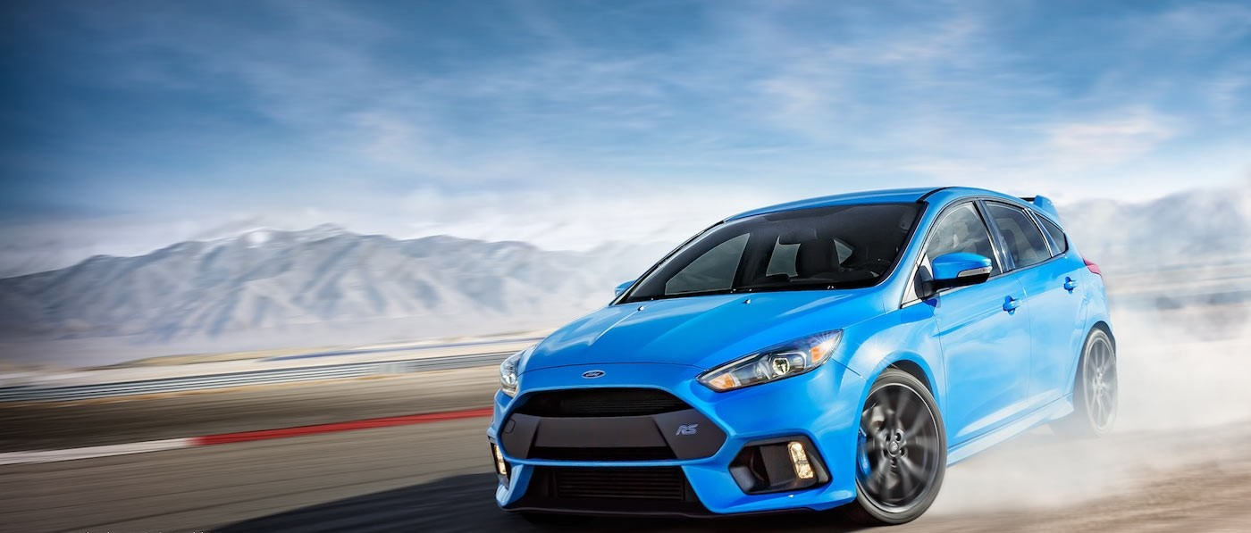 Light Blue 2017 Used Ford Focus drifting on a desert track with mountains in the distance