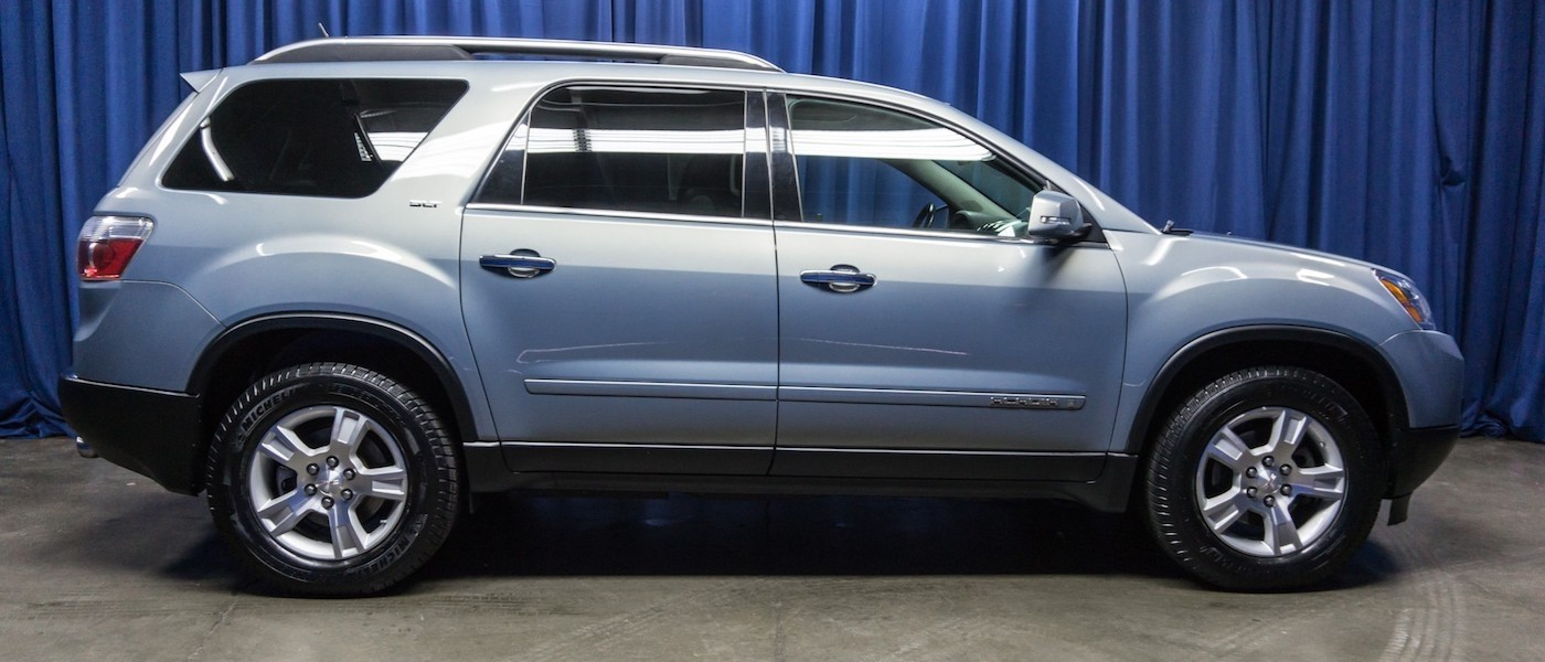 Profile of a Silver 2008 Used GMC Acadia parked in front of a blue curtain