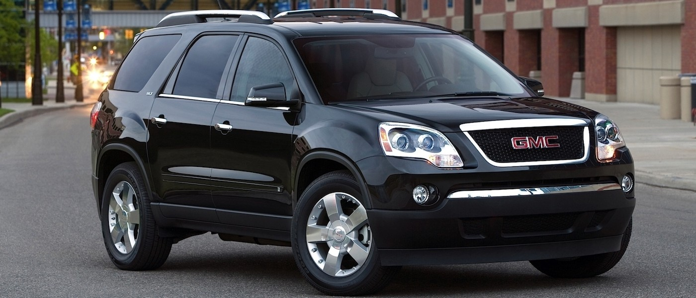 Black 2012 Used GMC Acadia parked in city street next to a parking garage