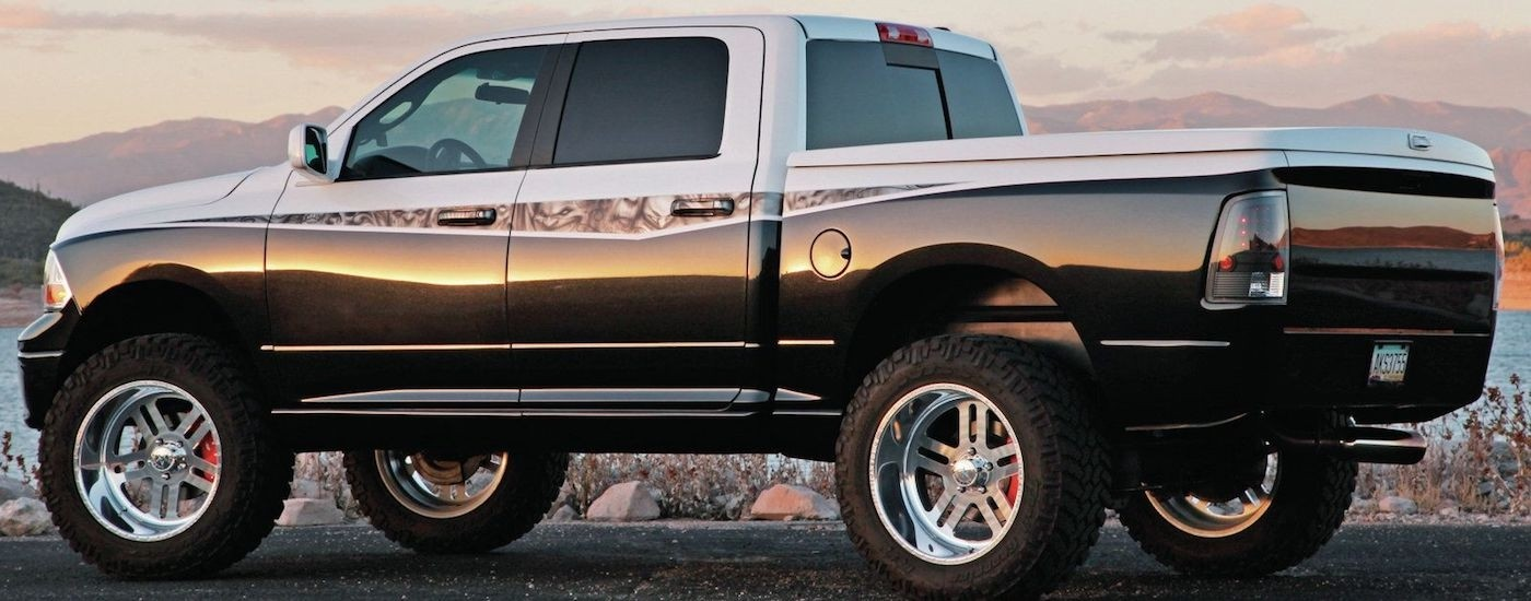 Custom black and white paint job on a lifted 2010 RAM 1500 with mountains in the back at dusk