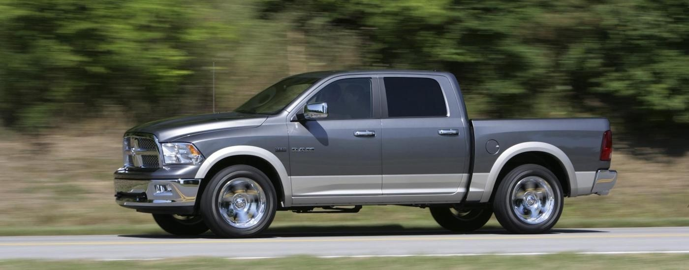 Silver and gray 2011 Used RAM 1500 driving on a tree-lined road