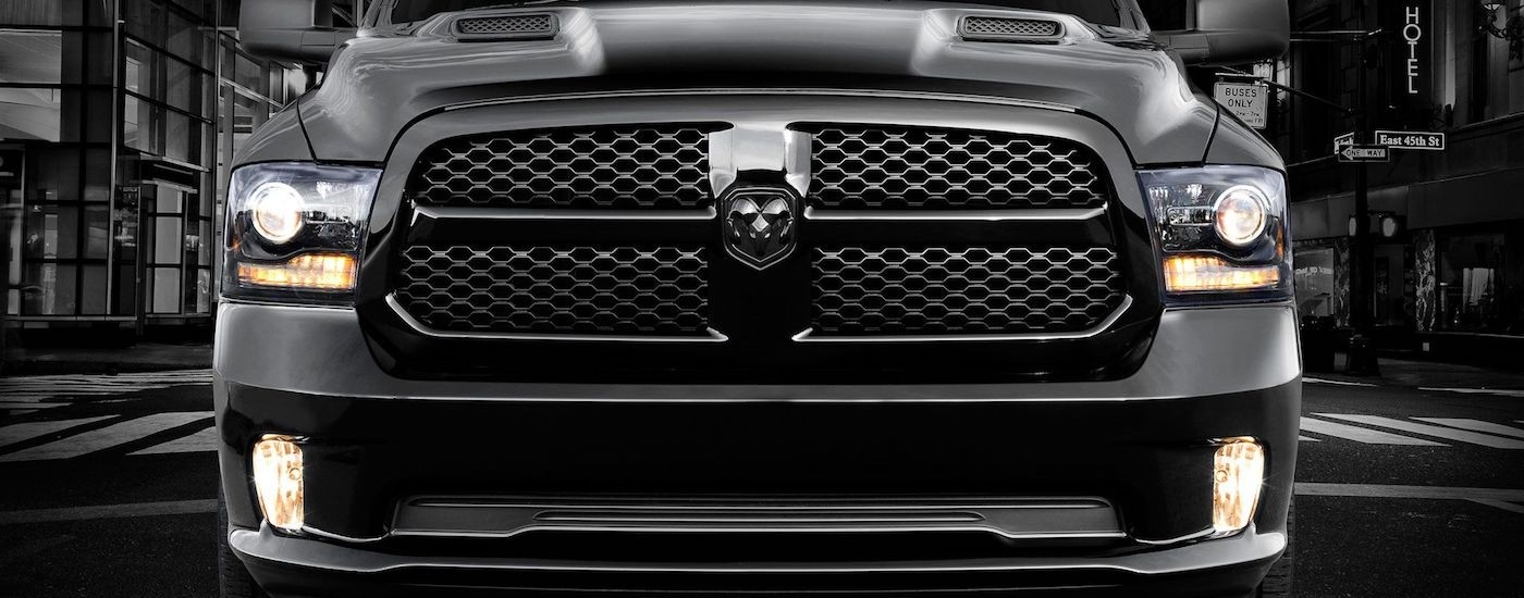 Closeup of the grille on a Black 2013 Used RAM 1500 in a city