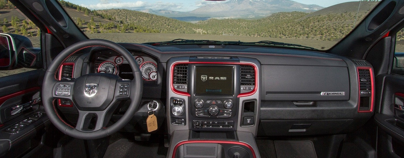 Black interior with red accents in a 2017 Used RAM 1500 overlooking mountains
