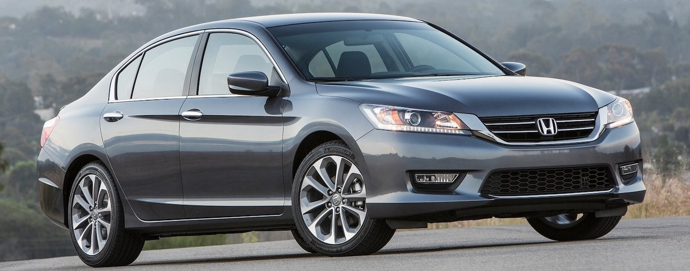 Gray 2013 Used Honda Accord on a hill with trees in the distance