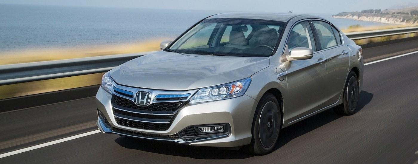 Silver 2014 Used Honda Accord driving down seaside road