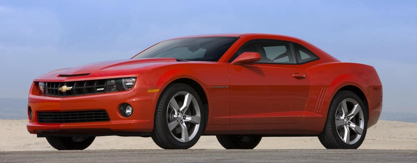 A red 2011 Used Chevy Camaro is shown in a desert against a blue sky